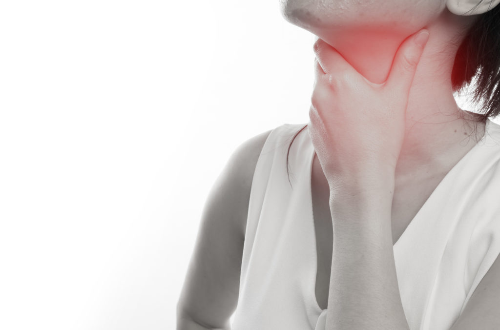 Woman touching highlighted area of her throat, sensing pain and discomfort.