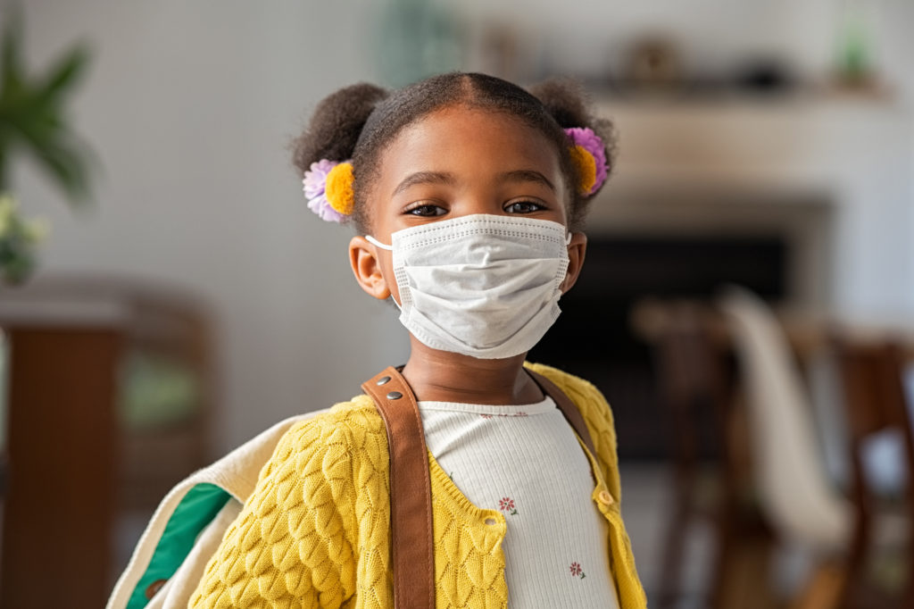 Little girl wearing a face mask and backpack
